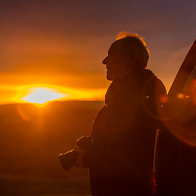 Senior man with camera at sunset - p1427m2169378 by Steve Smith