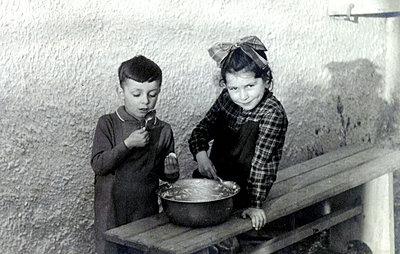 Siblings with spoons nibbling from a bowl - p1541m2172498 by Ruth Botzenhardt