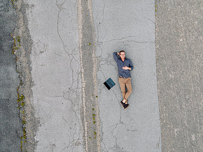 Young businessman with laptop relaxing in solitude, quadcopter view - p300m1535669 by Kniel Synnatzschke