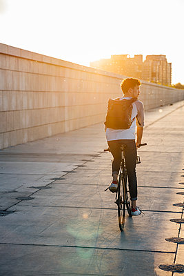 Young man with backpack riding bike on promenade at sunset - p300m2059657 by Vasily Pindyurin