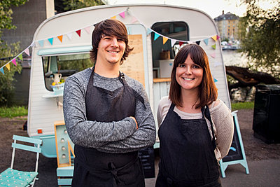 Portrait of happy owners standing on street against food truck - p426m1407059 by Maskot