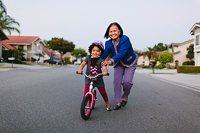 Grandmother teaching granddaughter to ride bicycle on suburban street - p555m1409612 by Shestock