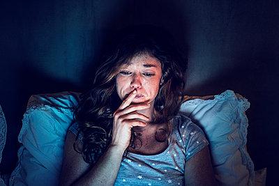 Weinende junge Frau im Bett - p586m1144083 von Kniel Synnatzschke