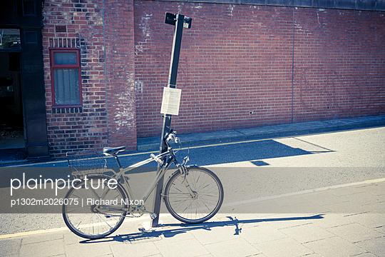 Mit Fahrradschloss befestigtes Fahrrad an einem Straßenschild  - p1302m2026075 von Richard Nixon