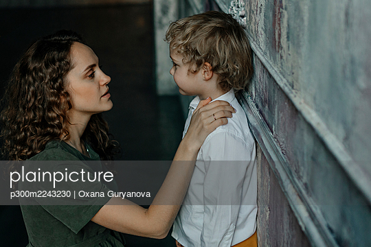 Mother looking at son leaning on wall - p300m2243230 by Oxana Guryanova