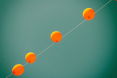 Low angle view of orange balloons hanging on wire against clear blue sky during sunny day - p1166m2060550 by Cavan Social