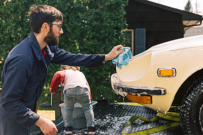 A father and his toddler daughter washing a classic car together. - p1166m2190652 by Cavan Images