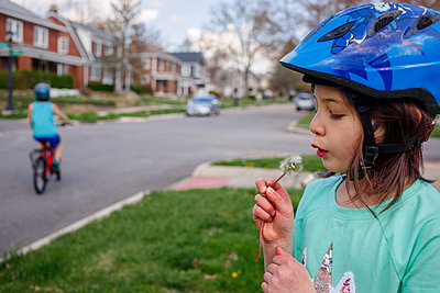 A little girl blows on dandelion while boy bikes on street behind her - p1166m2201114 by Cavan Images