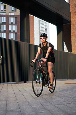 Woman cyclist in helmet on background of brick building in summer afternoon - p1630m2196884 by Sergey Mironov