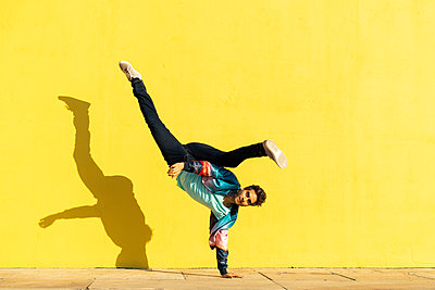 Acrobat doing movement training in front of a yellow wall - p300m2012270 by VITTA GALLERY