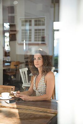 Mature woman sitting in coffee shop with smartphone and digital tablet - p300m2070587 by Robijn Page