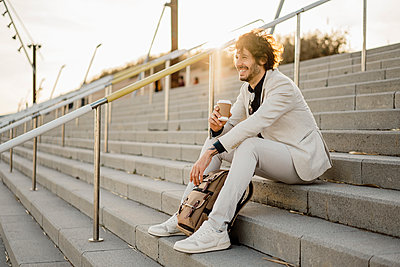 Laughing businessman with coffee to go and backpack sitting on stairs outdoors - p300m2113845 by VITTA GALLERY