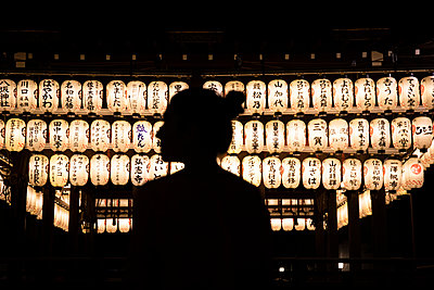 Japan, Kyoto Prefecture, Kyoto City, Silhouette of woman admiring rows of lanterns glowing in Japanese temple at night - p300m2197170 by Andrés Benitez
