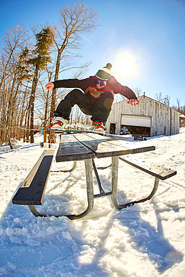 Snowboarder ollieing picnic table, Vermont, USA - p343m1577981 by Josh Campbell