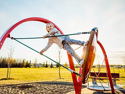A daring young girl playing on a saucer swing in a playground on a warm autumn evening; Edmonton, Alberta, Canada - p442m2012187 by LJM Photo