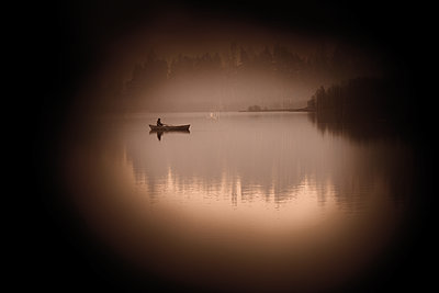 Fisherman in his boat on the lake at dawn - p945m2177739 by aurelia frey