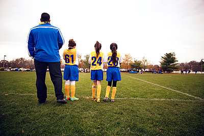 Rear view of soccer players standing with coach on playing field - p1166m1038251f by Cavan Images