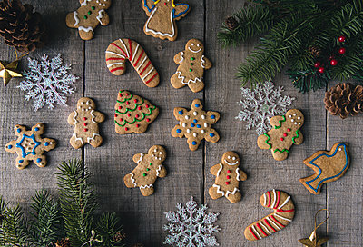 Overhead view of decorated gingerbread cookies on wooden table - p1166m1555001 by Cavan Images