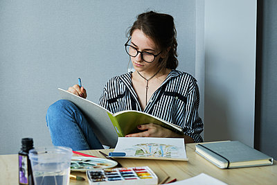 millennial girl draws fabulous images on paper while sitting at home - p1166m2171824 by Cavan Images