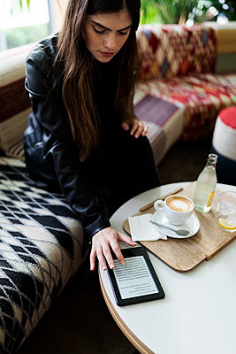 Young woman sitting in a cafe using e-book - p300m2069534 by Valentina Barreto