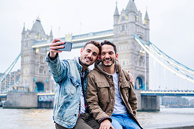 Two young tourists sitting on wall, using smartphone, with  London Bridge in background - p300m2170004 by Daniel González