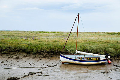 Fishing boat in mud of small estuary - p644m717598 by Naki Kouyioumtzis