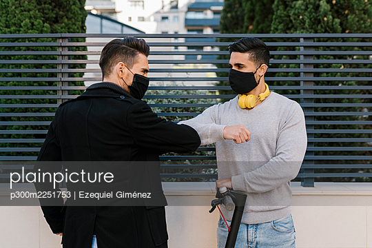 Male friends greeting each other by giving elbow bump wearing protective face mask against metal fence during COVID-19 - p300m2251753 by Ezequiel Giménez
