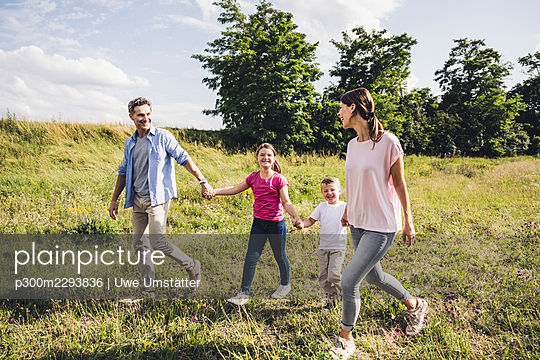 Smiling family holding hands while walking on grass - p300m2293836 by Uwe Umstätter