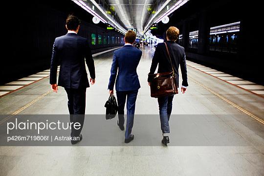 Rear view of three businessmen walking on railway station platform