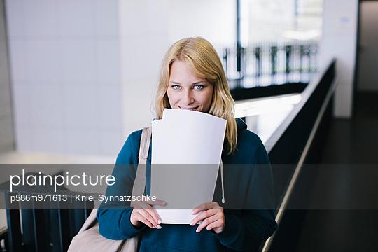Blonde Studentin mit Dokumenten in der Hand - p586m971613 von Kniel Synnatzschke