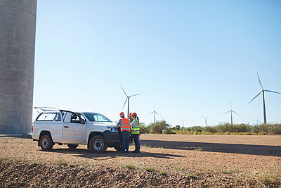 Engineers meeting at truck at sunny wind turbine power plant - p1023m1583993 by Trevor Adeline