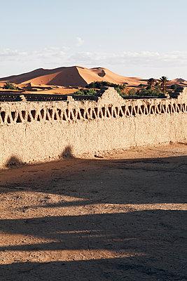 Blick über eine Mauer auf die marokkanische Wüste - p1150m1586600 von Elise Ortiou Campion