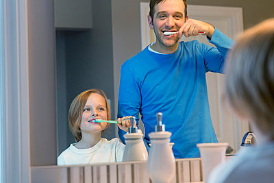 Father and son brushing teeth together in bathroom. - p328m840978f by Hero Images