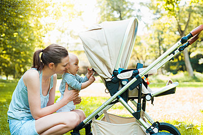 Mother and daughter playing by pram in park - p429m1494650 by Daniel Ingold