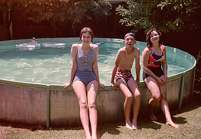 Portrait of Caucasian brother and sisters leaning on swimming pool - p555m1444178 by PBNJ Productions