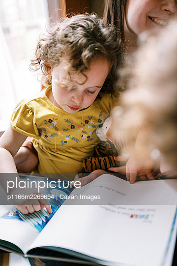 A child sitting on her mothers lap reading a book together on stairs - p1166m2269694 by Cavan Images