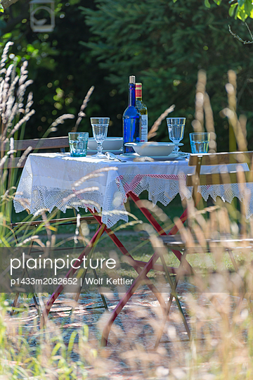 A table is set for two on a rug in a summer garden. - p1433m2082652 by Wolf Kettler