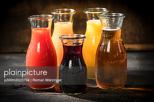 Glass bottles of various fruit juices - p300m2023794 von Roman Märzinger