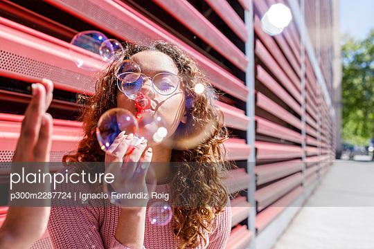 Playful young woman blowing bubbles on sunny day - p300m2287724 by Ignacio Ferrándiz Roig