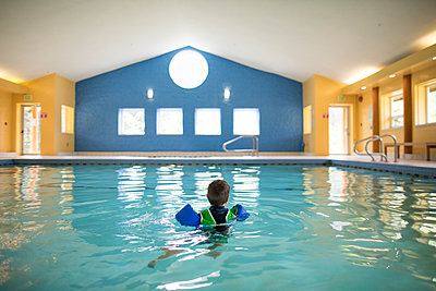 Toddler boy swims alone in indoor pool. - p1166m2094987 by Cavan Images
