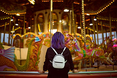 Rear view of young woman standing against illuminated carousel - p1315m1484319 by Wavebreak