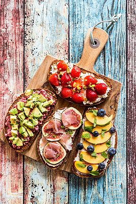 Various sandwiches, strawberry, fig, nectarine, avocado, on chopping board - p300m1537709 by Sandra Roesch