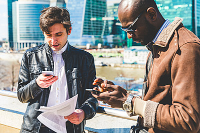 Russia, Moscow, two businessmen using smartphones in the city - p300m2013238 by William Perugini