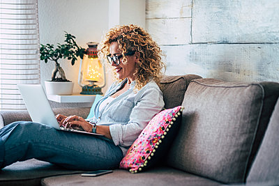 Smiling woman using laptop on couch at home - p300m2103878 by Simona Pilolla