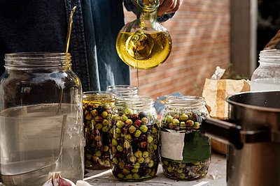 Barcelona, Spain. Mature man preparing olives in jars to be cured - p300m2242308 von VITTA GALLERY