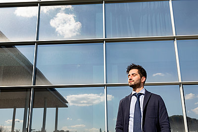 Mid adult businessman standing with eyes closed in front of office building - p300m2281754 by Emma Innocenti