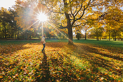 Mother in autumn leaves in Sweden - p352m1536609 by Calle Artmark