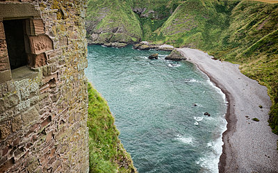 Castle wall cliffs beach waves from above view - p609m1219844 by OSKARQ