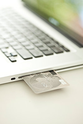 Credit card sticking out of side of laptop computer - p623m894316f by Gabriel Sanchez