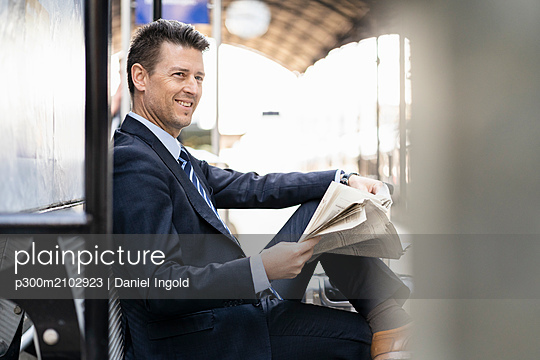 Smiling businessman reading newspaper on station platform - p300m2102923 by Daniel Ingold